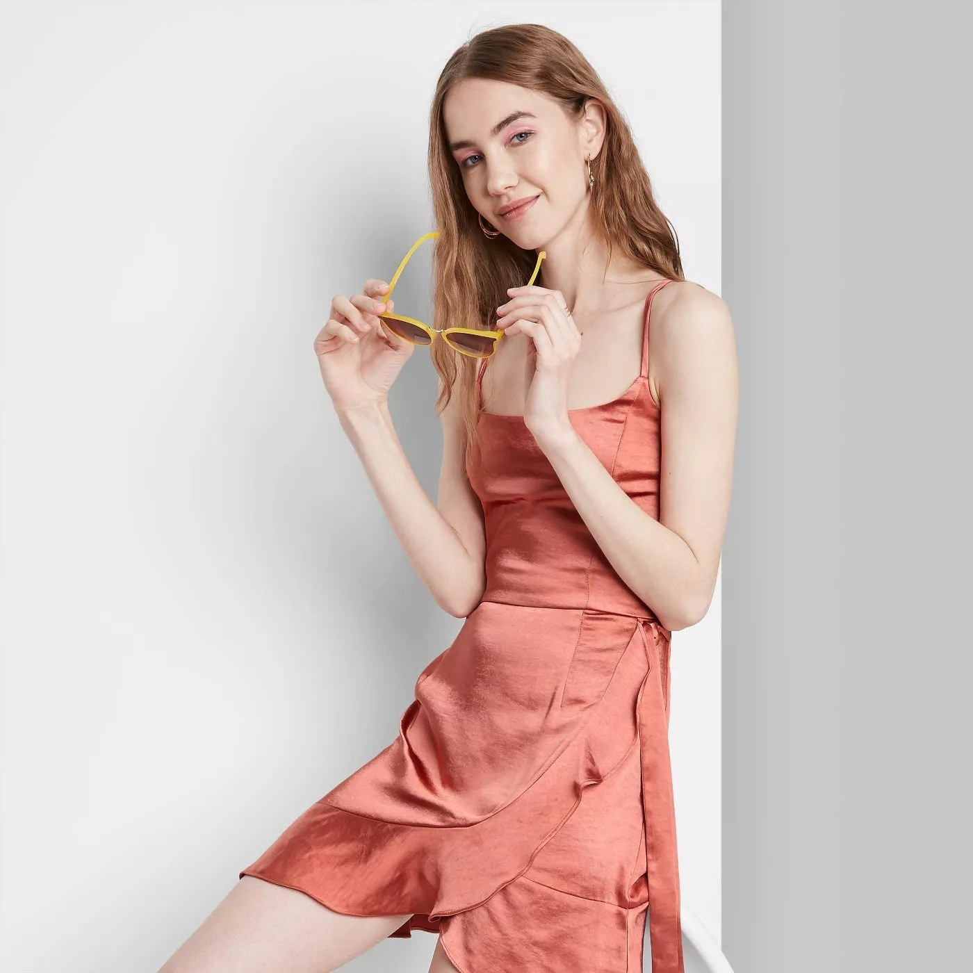 Model wearing orange silk dress with wrap around skirt, goes past the thigh
