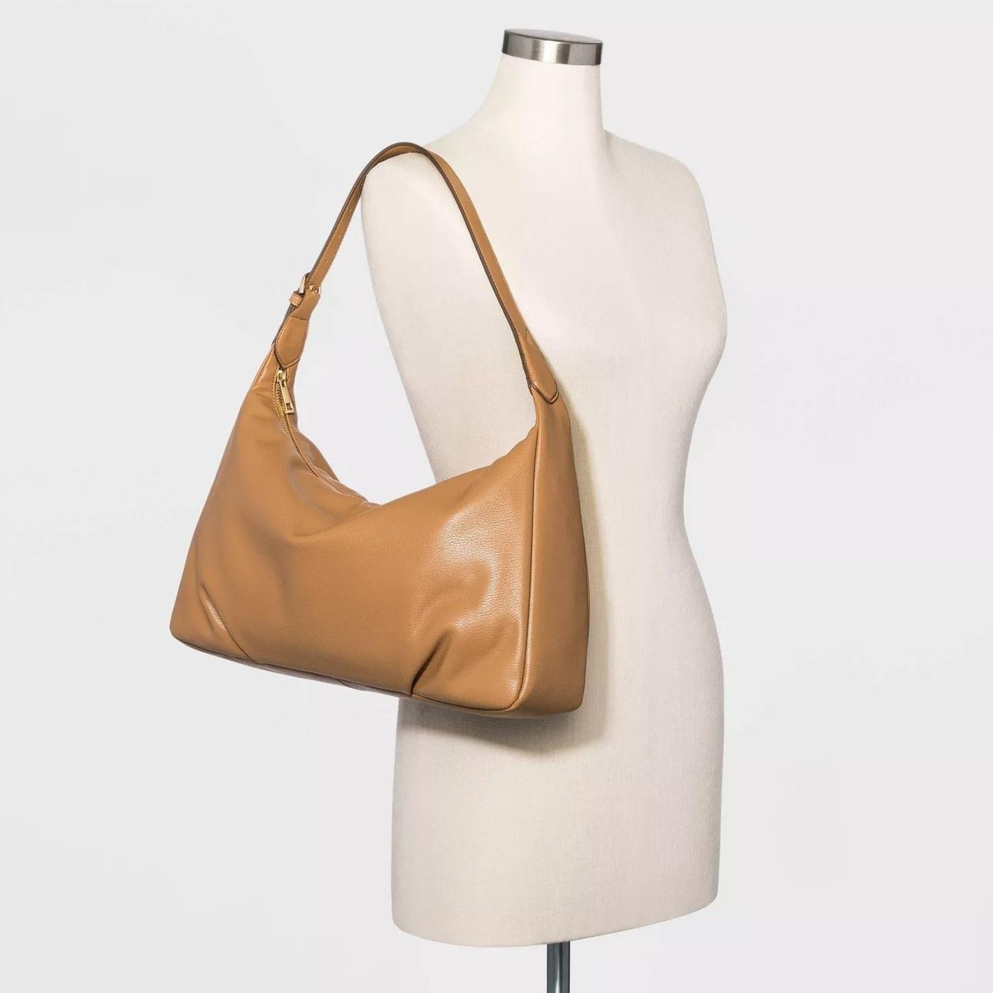 Dark beige rectangular purse with gold zipper, scoop handle
