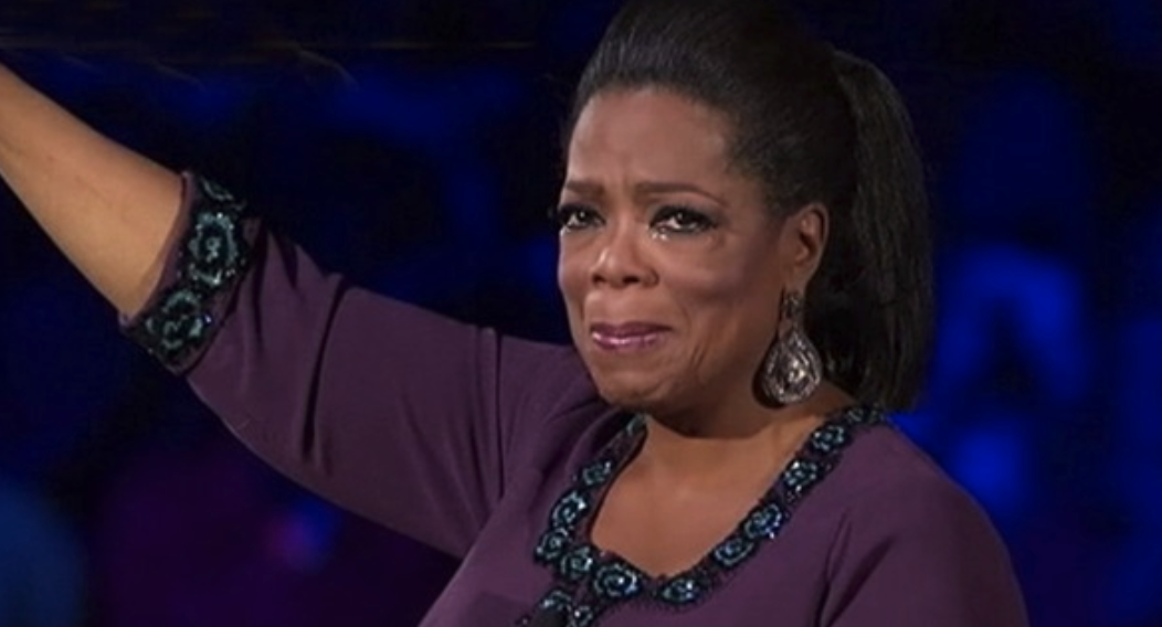 Oprah crying with one arm raised