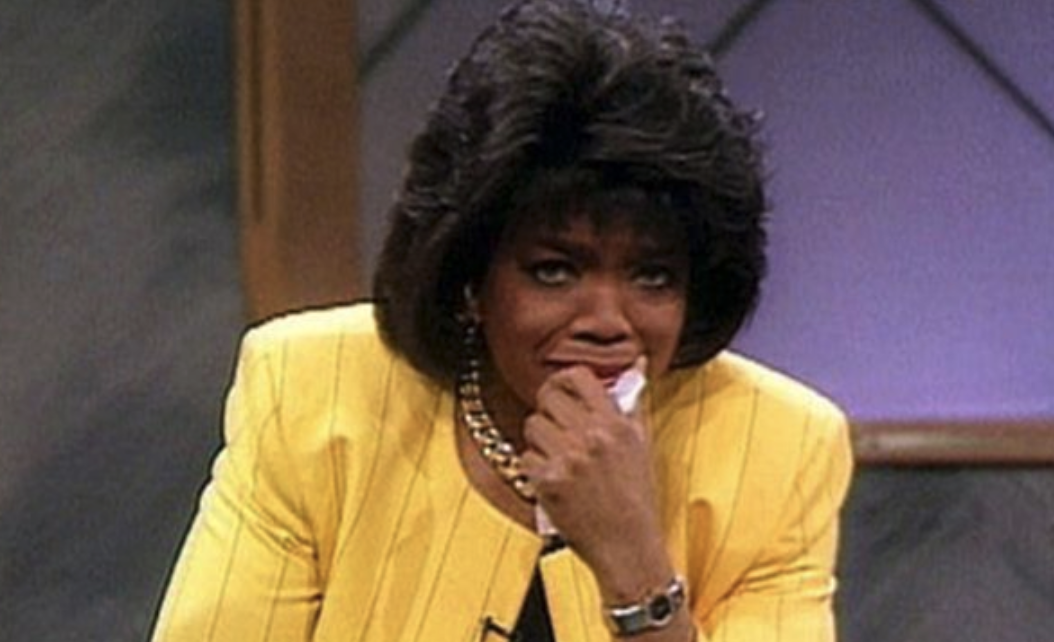 Oprah looking sad with her hand to her mouth