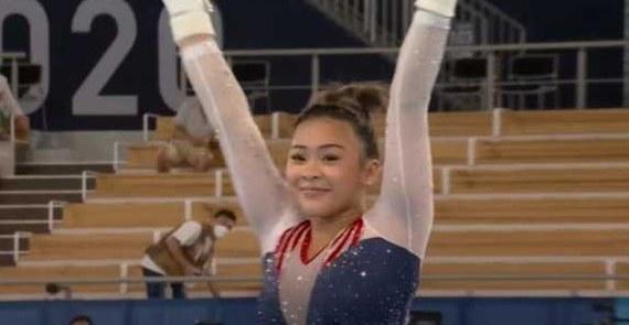 Suni Lee raising her arms after landing