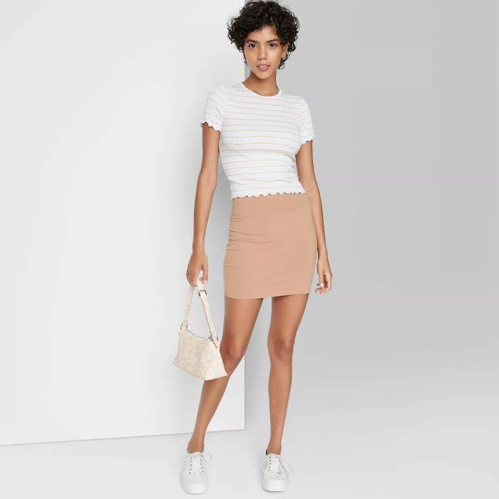 Model wearing tight light beige skirt, stops at the thigh