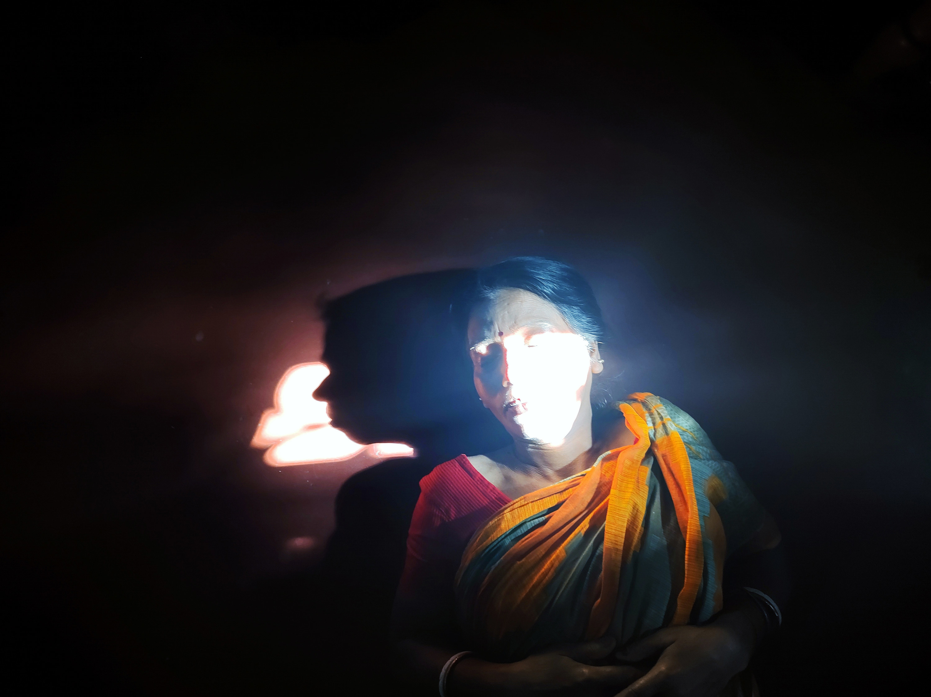A woman in a sari with a bright light flashing across her