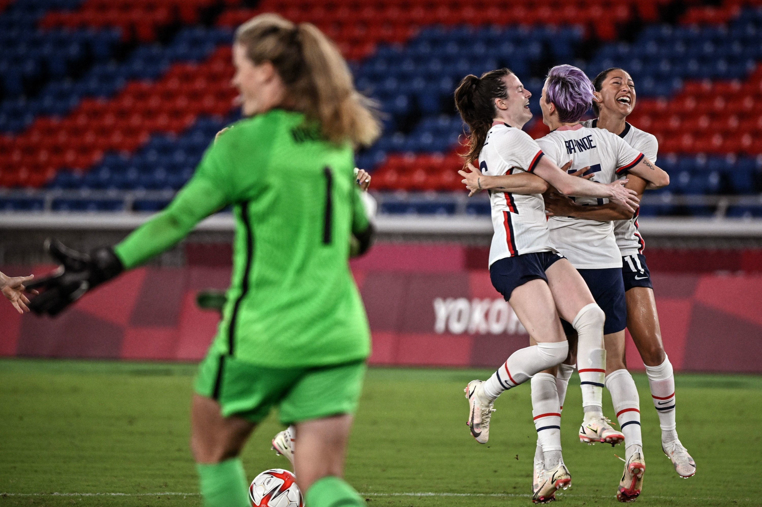Smiling soccer players embrace in a group hug on the field
