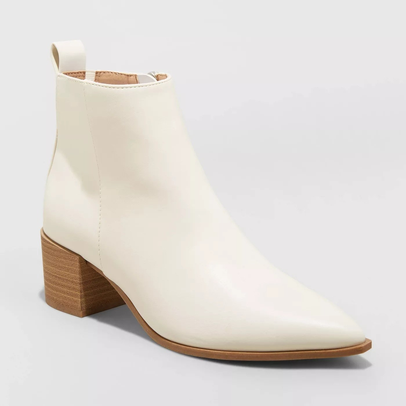 White ankle boots with pointy toe and oak colored sole, medium sized heel