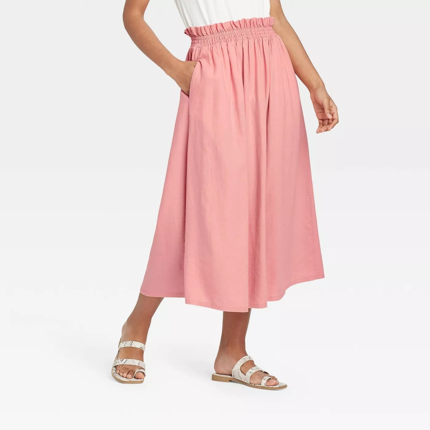 Model wearing pink maxi skirt with elastic waistband, stops above the ankle