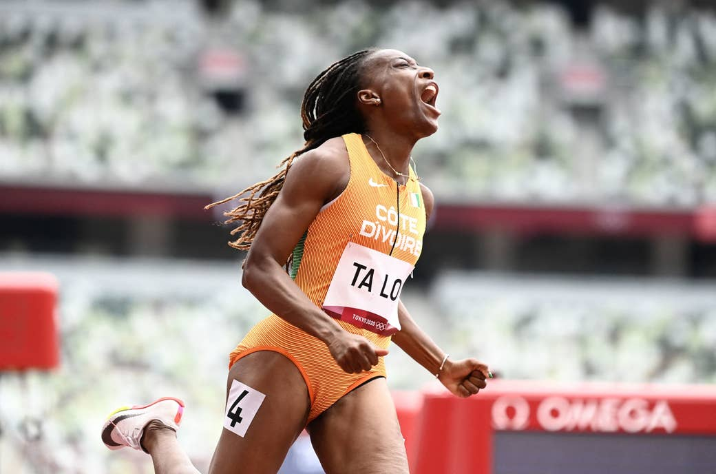 A person clenches their fists and screams as they run through the finish line on the track at the Tokyo Olympics