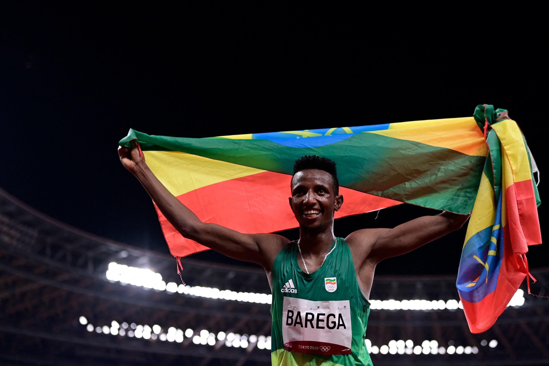 Athlete Selemon Barega holds up an Ethiopian flag and grins