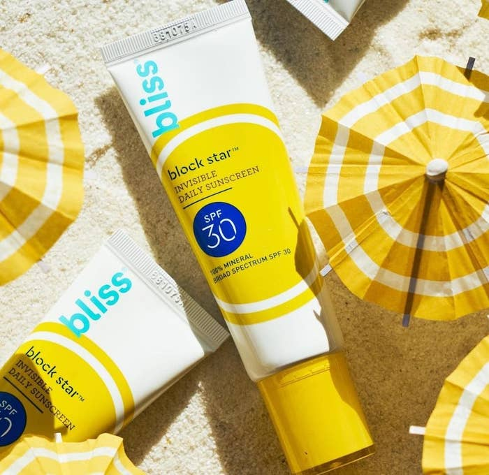 Bottles of Bliss Block Star mineral sunscreen on sand next to umbrellas