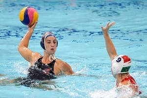 two water polo players in the water while one is holding the ball
