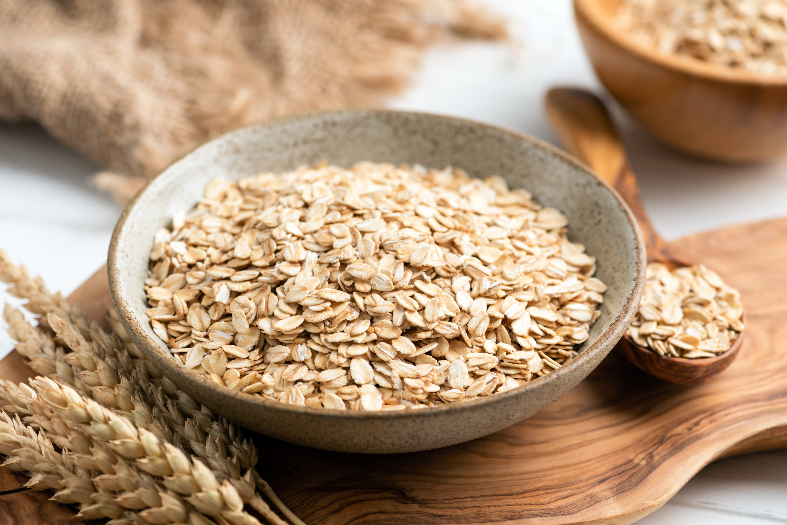 Rolled oats, oat flakes in bowl on wooden table.