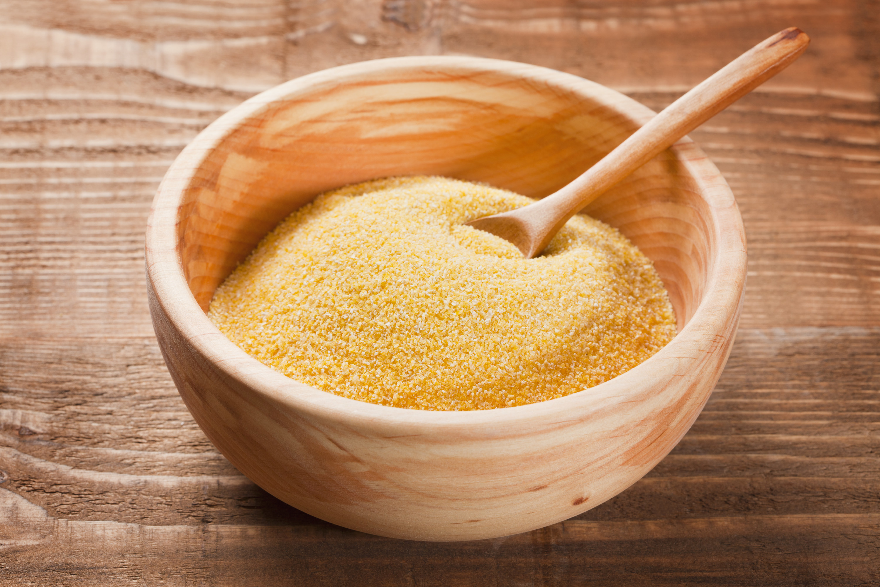 Corn grits in wooden dish with wooden spoon on the wooden rustic table