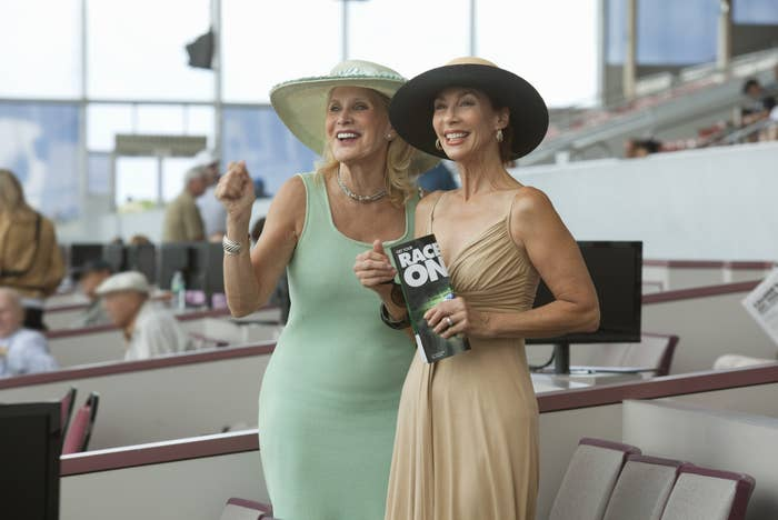 Two women at a horse race wearing dresses and matching wide-brimmed hats