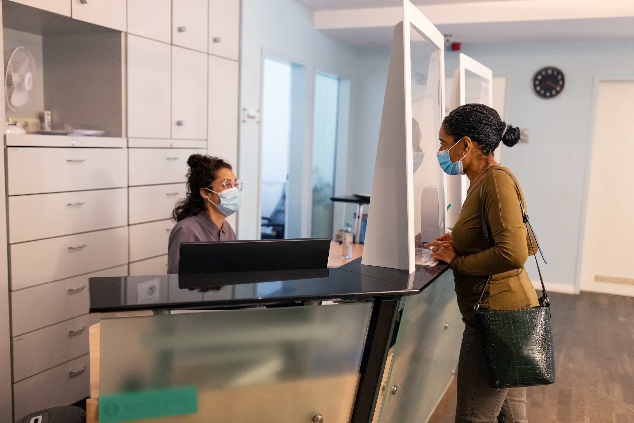 A person, wearing a face mask, talking to a receptionist, who's also wearing a face mask