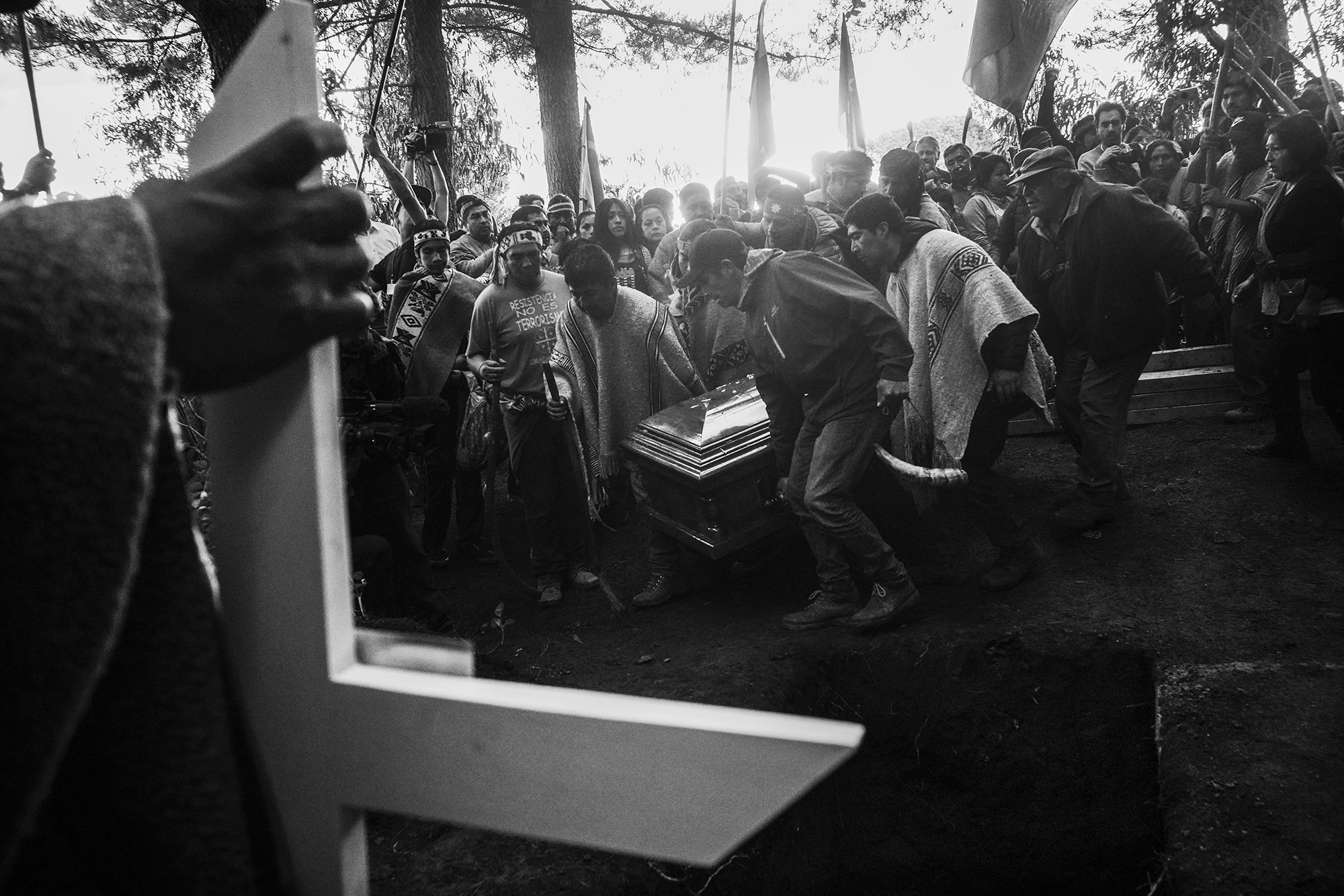 Pallbearers carry coffin through crowd of mourners