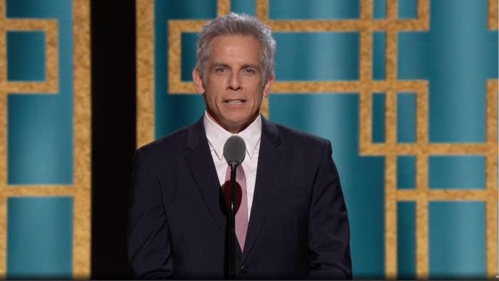 Ben Stiller speaking on stage in a suit and tie