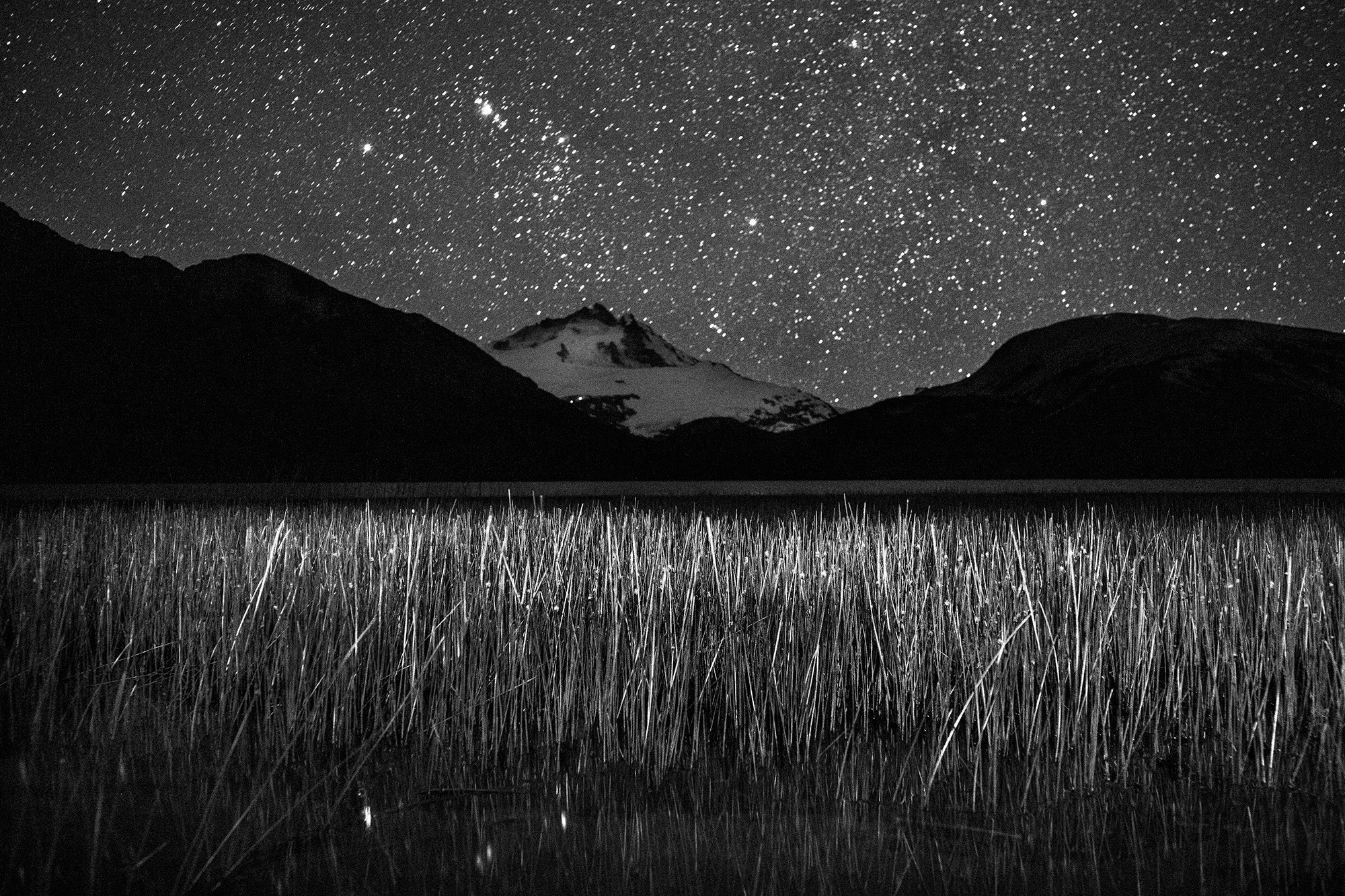 Stars shine over field and mountains