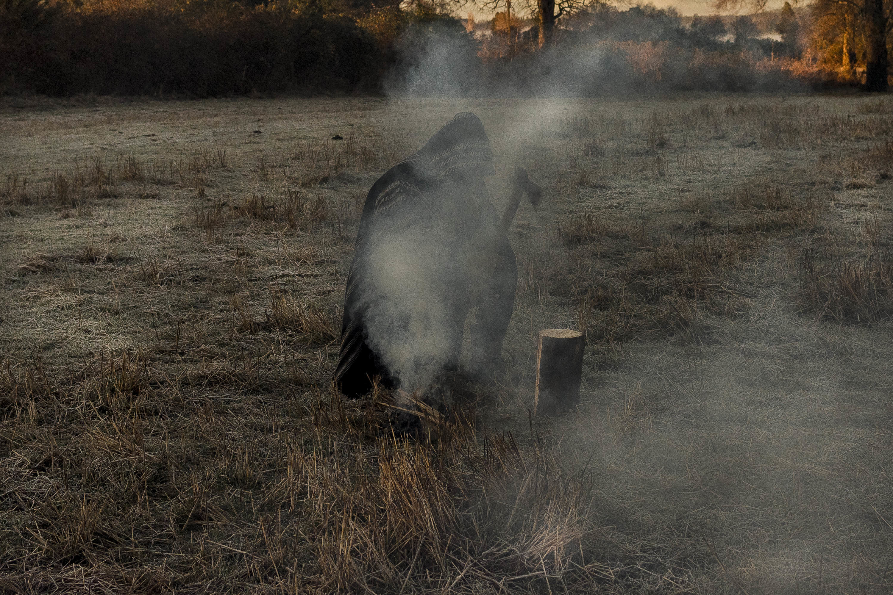 Man stands in field with smoke