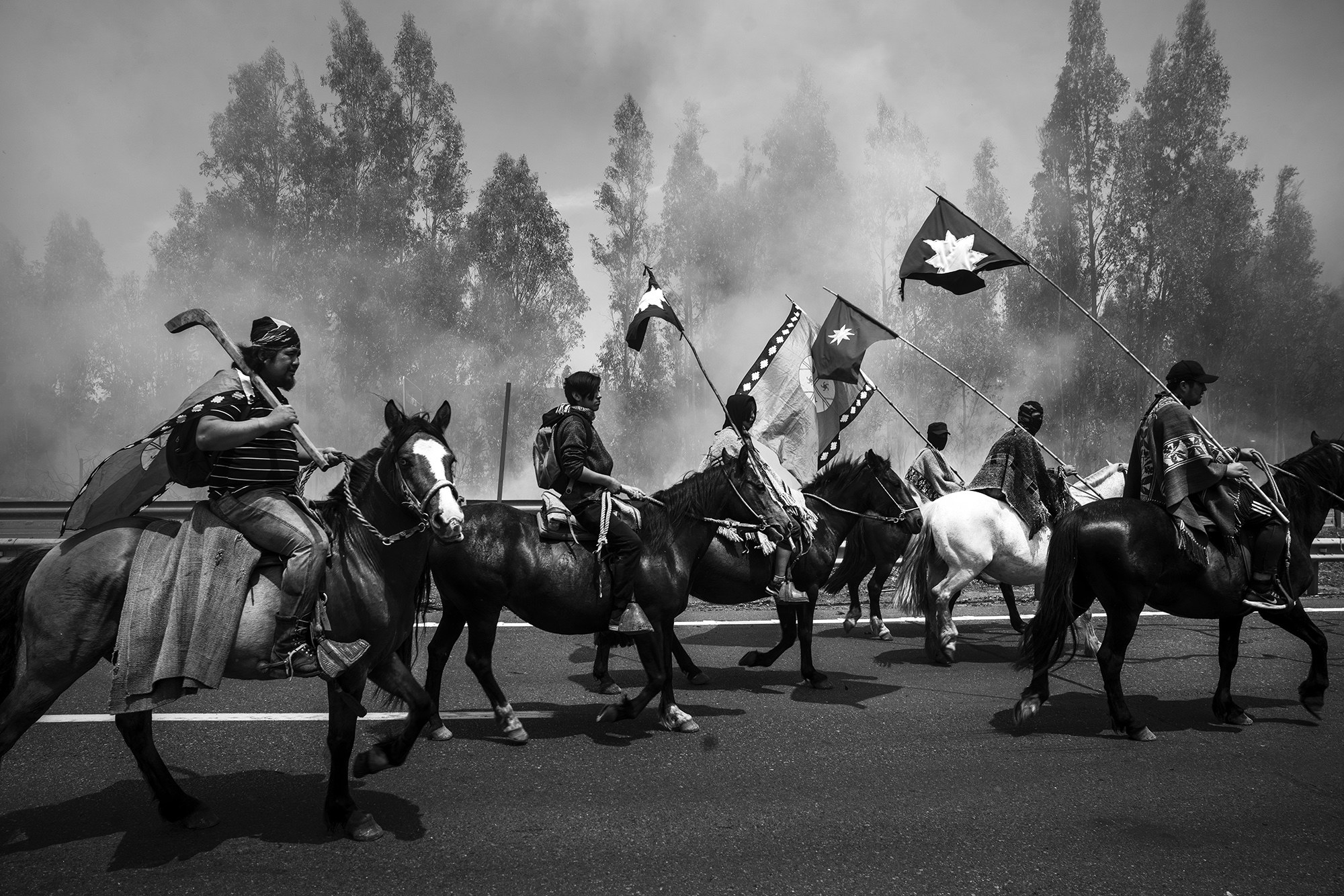 People ride horses and carry flags