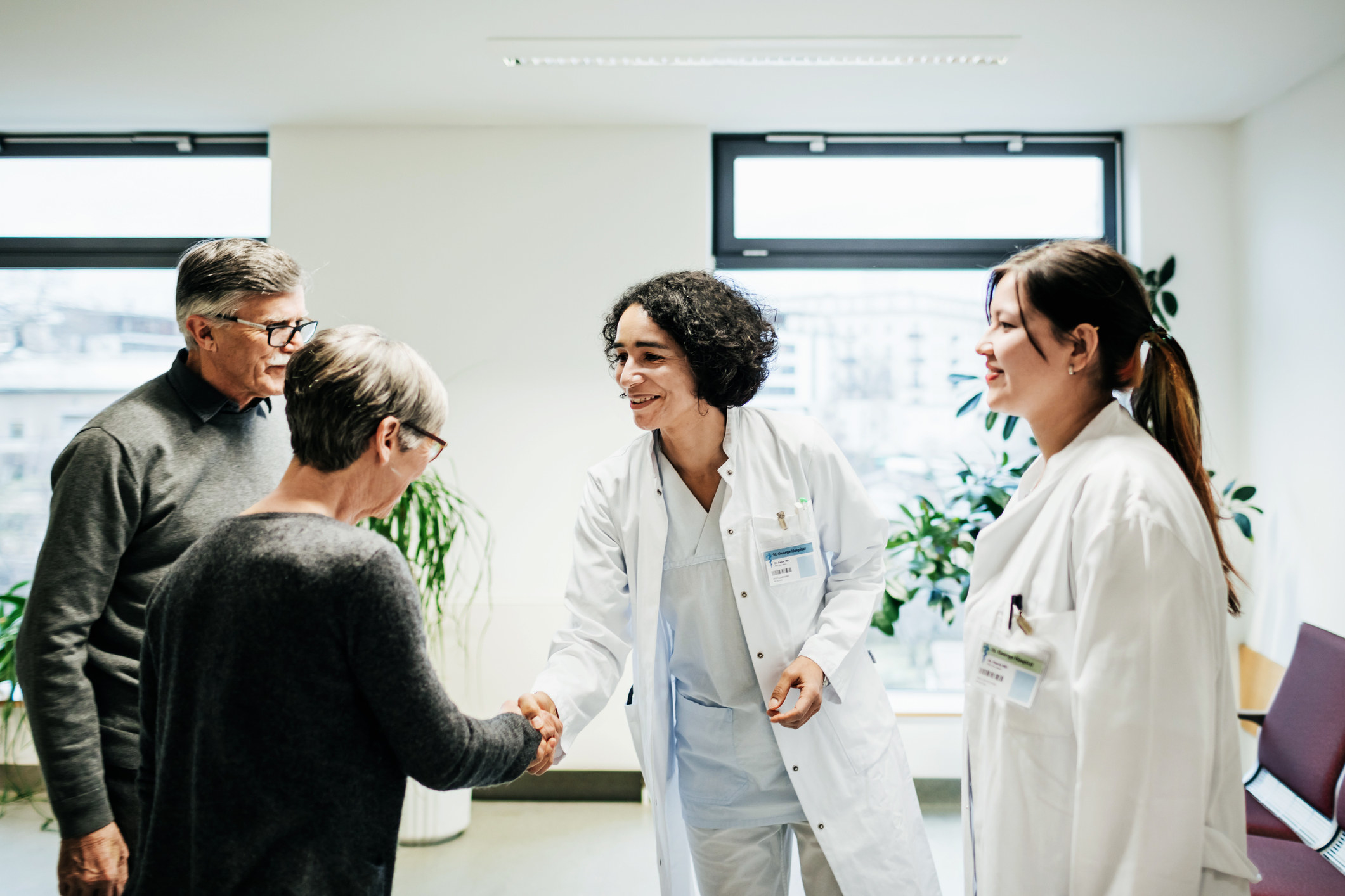 Two older people shaking hands with two doctors