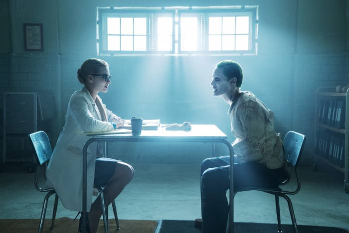 Harley Quinn and The Joker, in a straight jacket, sitting at a table and talking to one another