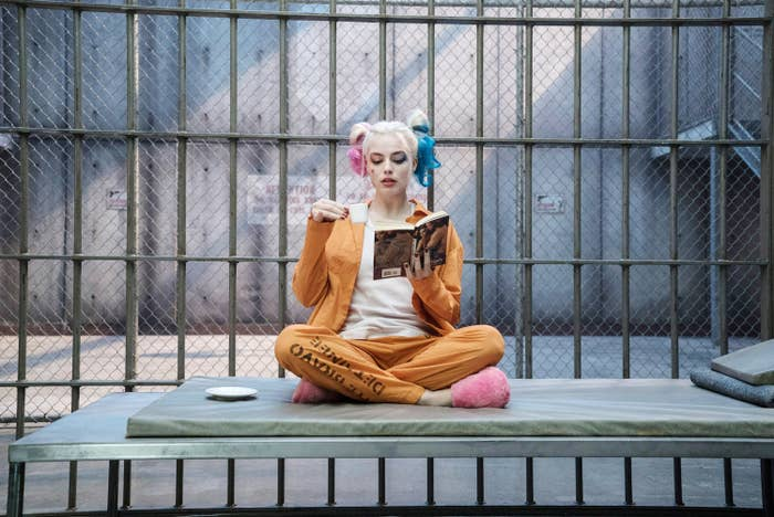 Harley Quinn siting cross-legged and sipping an espresso while reading a book in her jail cell