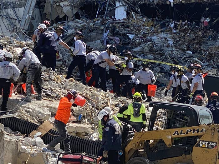 Rescue workers hand debris to one another in the rubble