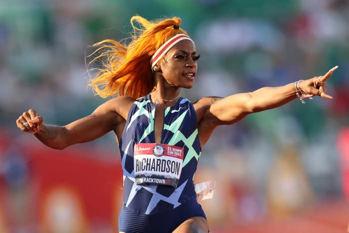 Sha'Carri pointing at her time as she crosses the finish line