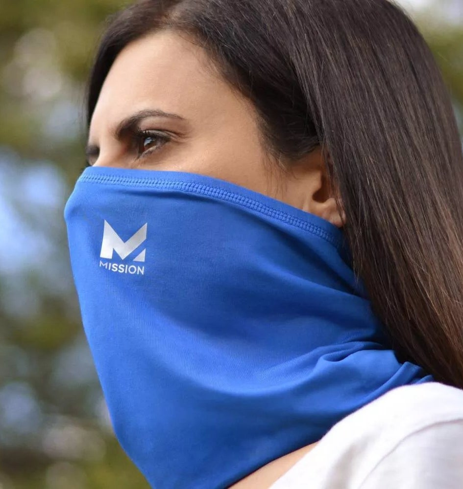 A model wearing the blue Mission gaiter as a face mask