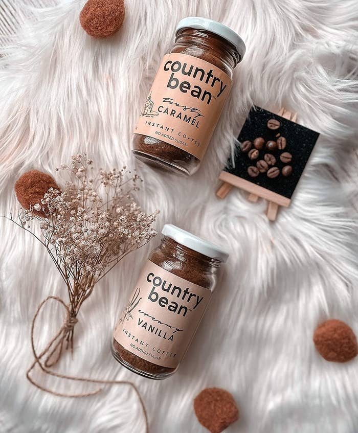 Two jars of caramel and vanilla instant coffee from Country Bean placed over a white fur rug.