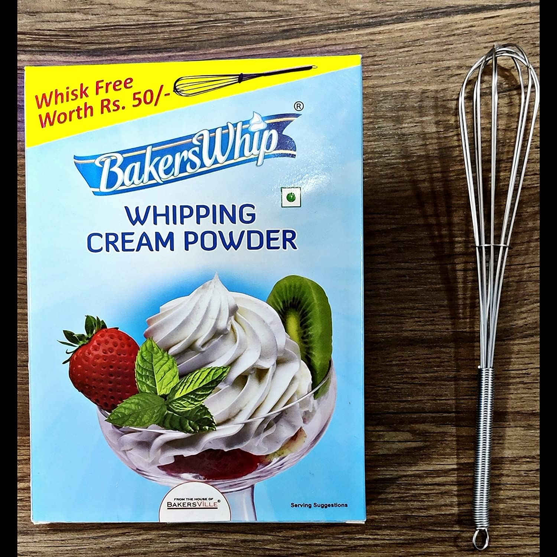A box of whipping cream powder kept alongside a whisk.