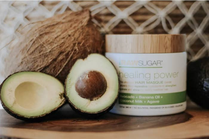 A jar of hair mask with a cut avocado and coconut