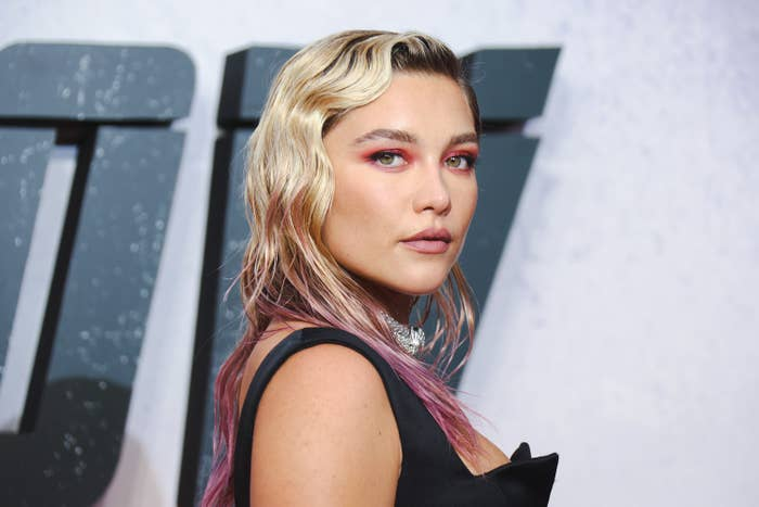 Florence Pugh, with hair of several tones, turns her head and looks at the camera