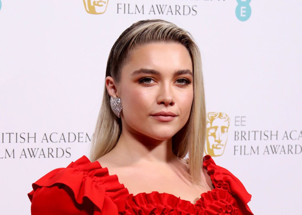 Florence Pugh in a frilly red top on the British Academy Film Awards red carpet