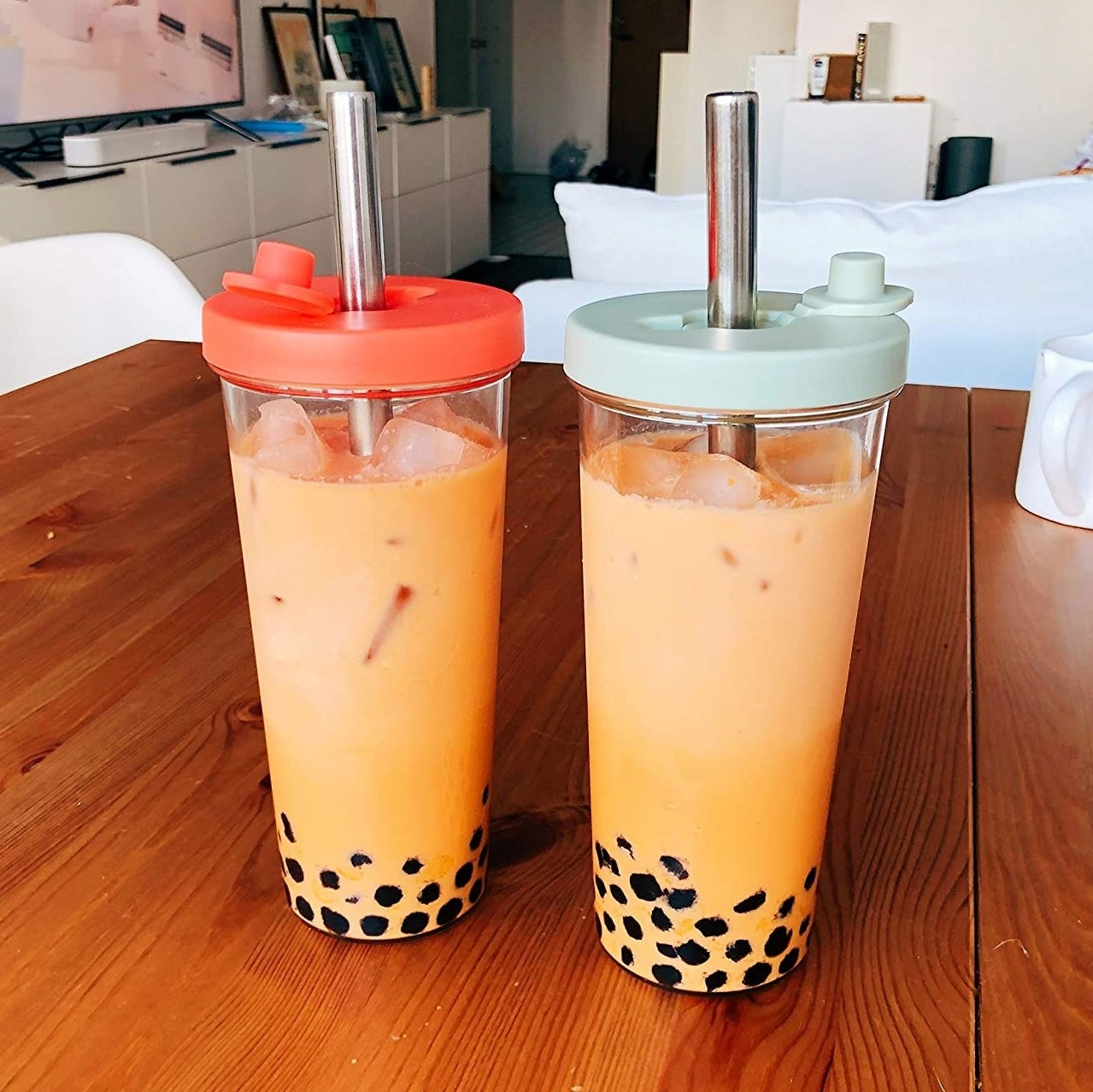 Two reusable boba cups filled with bubble tea