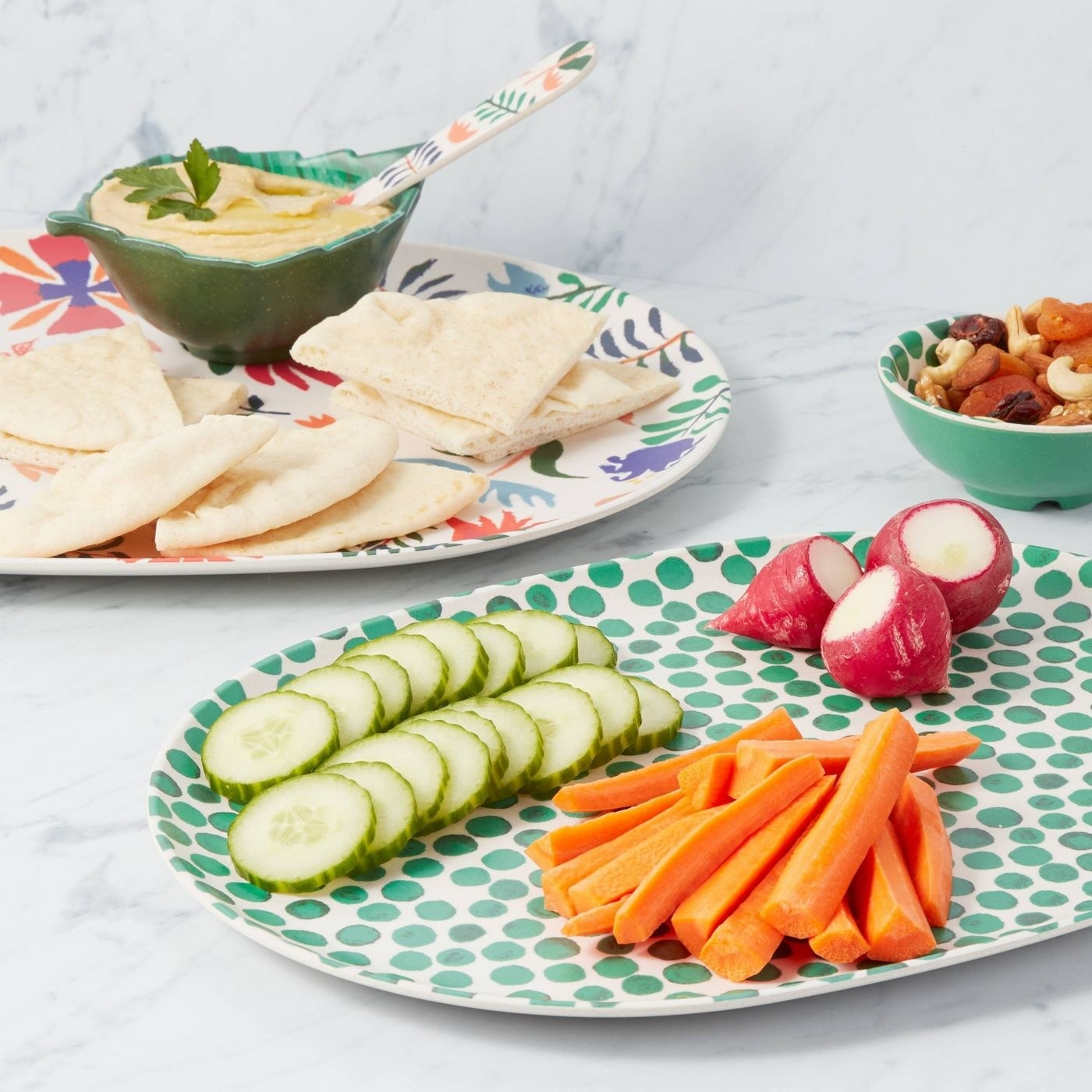 colorful dotted and floral trays holding veggies and pita