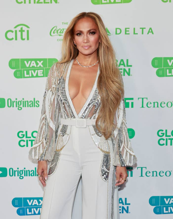 Jennifer Lopez smiles for cameras while on the red carpet wearing a white and silver outfit.