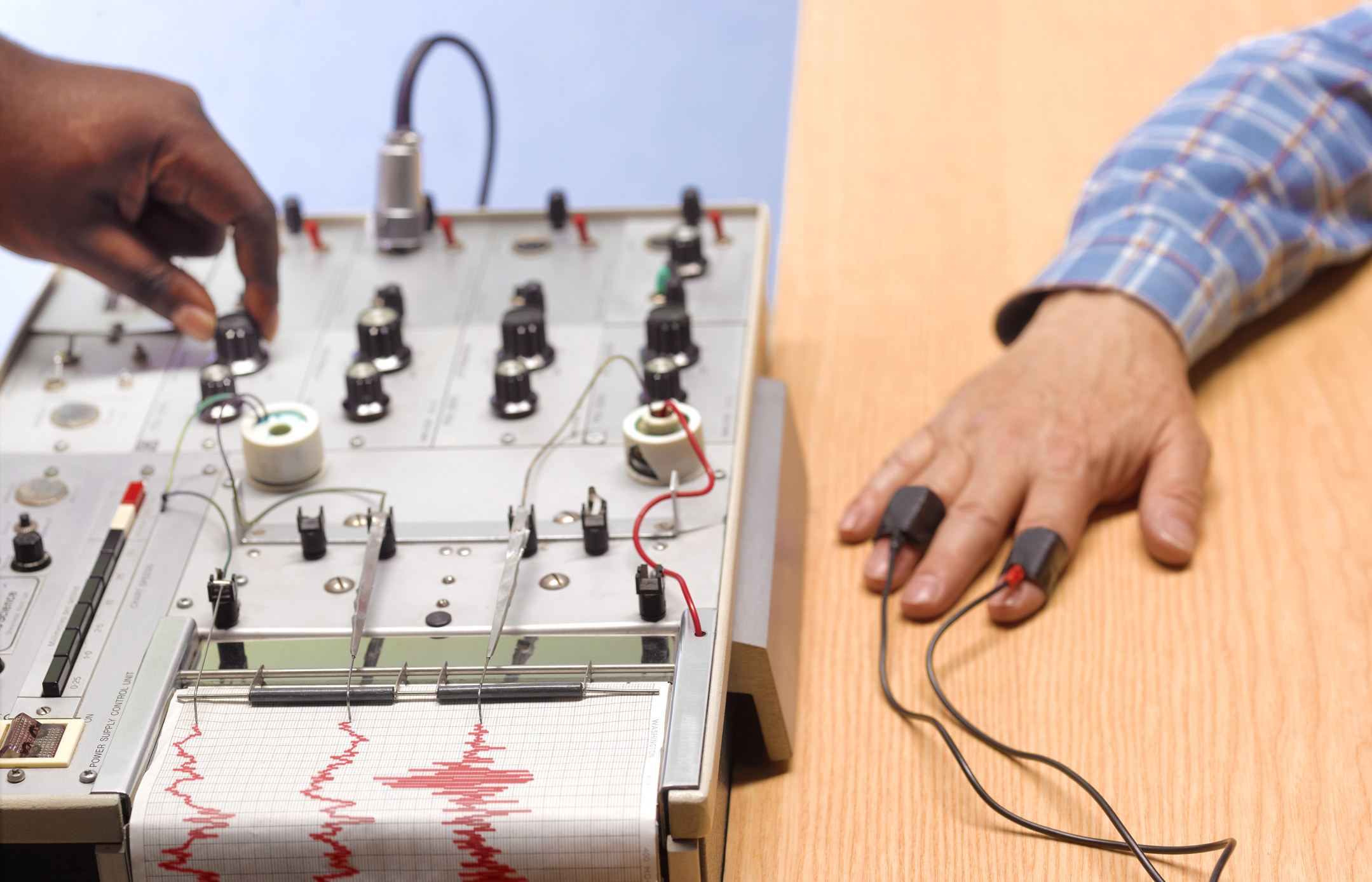 A polygraph test with a hand on one knob across from a man's hand on the table connected by sensors on index and ring fingers