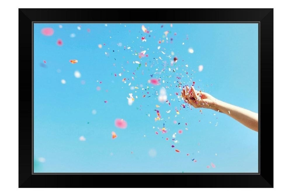 a photo print of a hand throwing confetti in a black frame