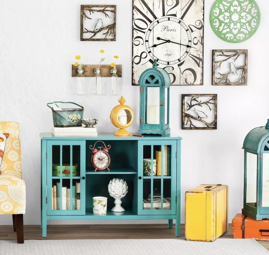 a teal storage cabinet with two glass doors and a shelf, holding decor