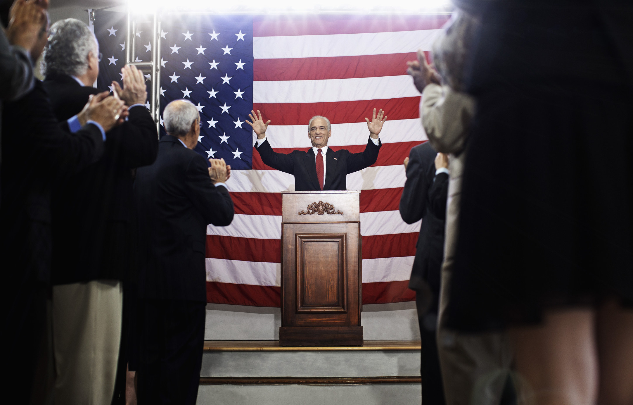 A politician at a podium with hands up toward the crowd, an American flag behind, and a group of people watching and clapping