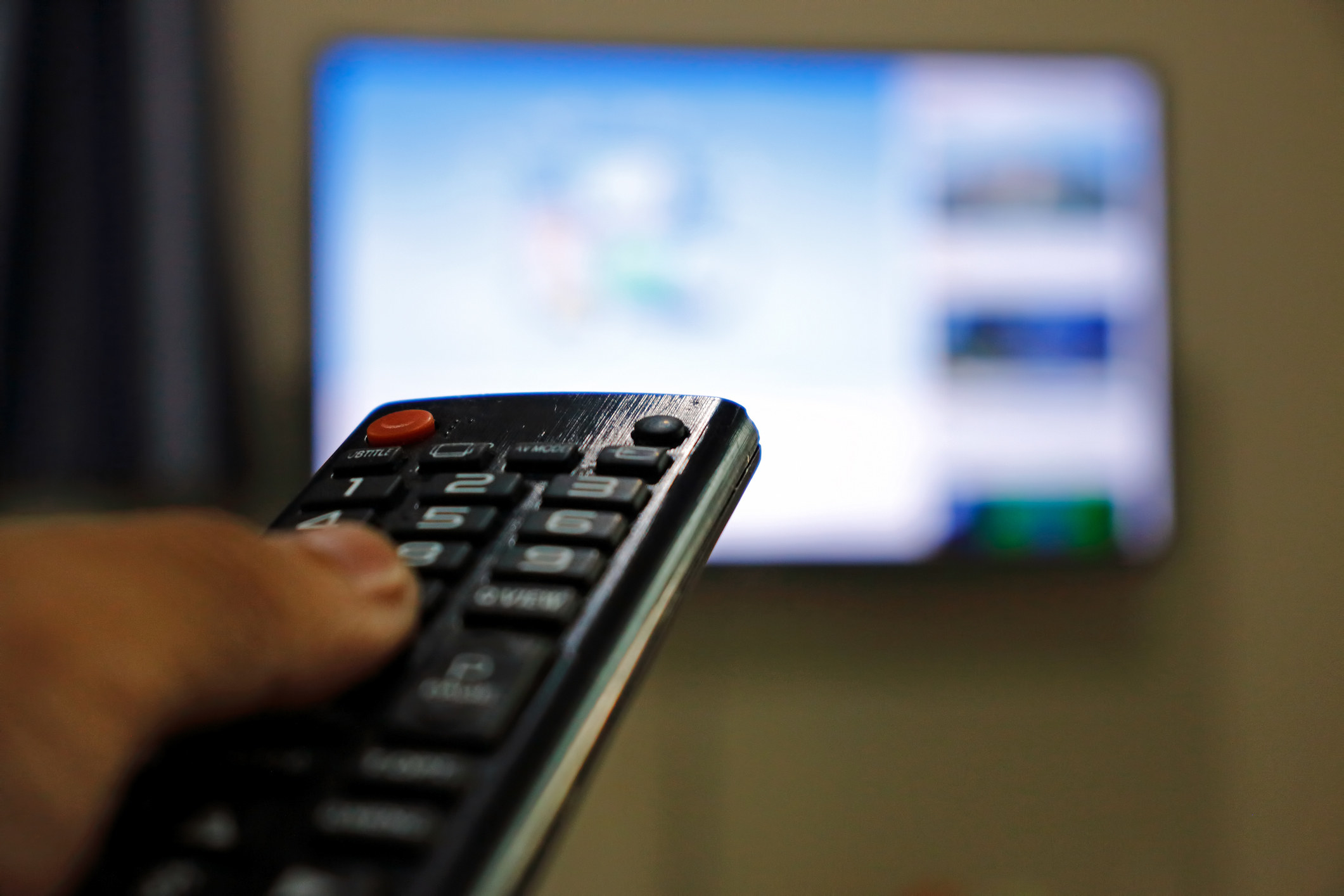 Close-up of a remote with someone's thumb on it being pointed towards a blurry TV screen mounted on the wall