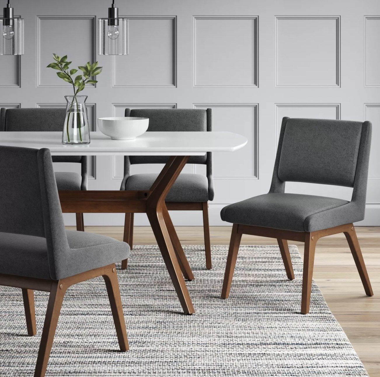 a grey upholstered dining chair with a backrest and tan wooden legs