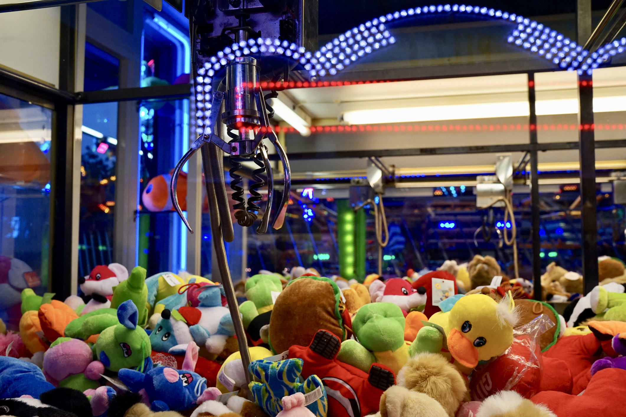 View from inside a claw machine just above a layer of toys with claw hanging over