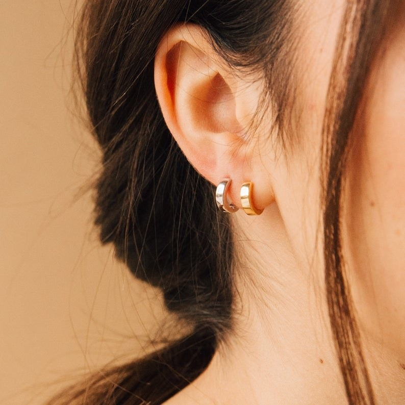 Model wearing the thick huggie hoops — one in gold and one in silver