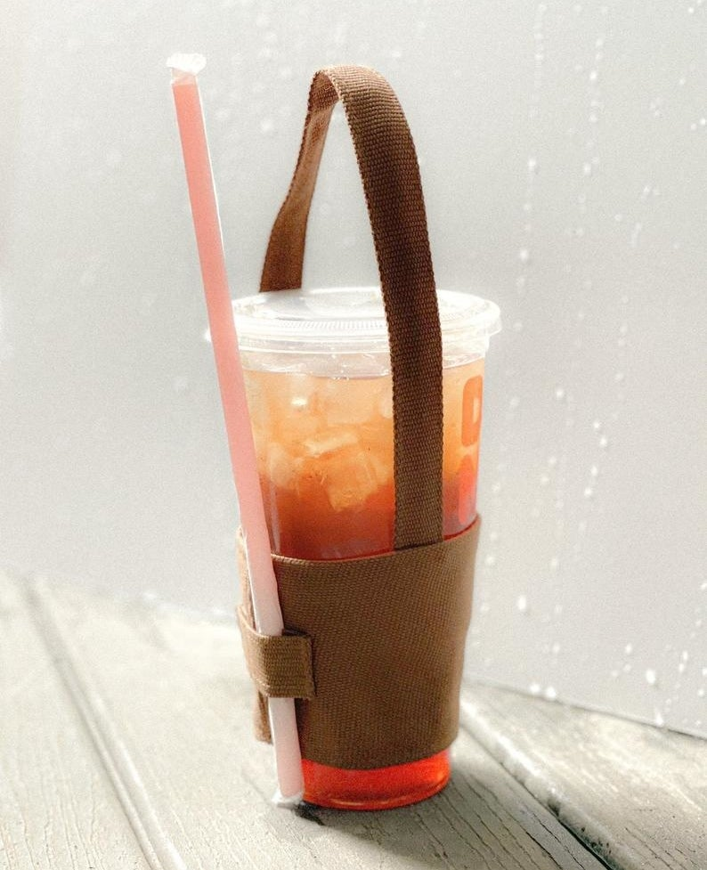 The coffee cup holder holding a drink and straw