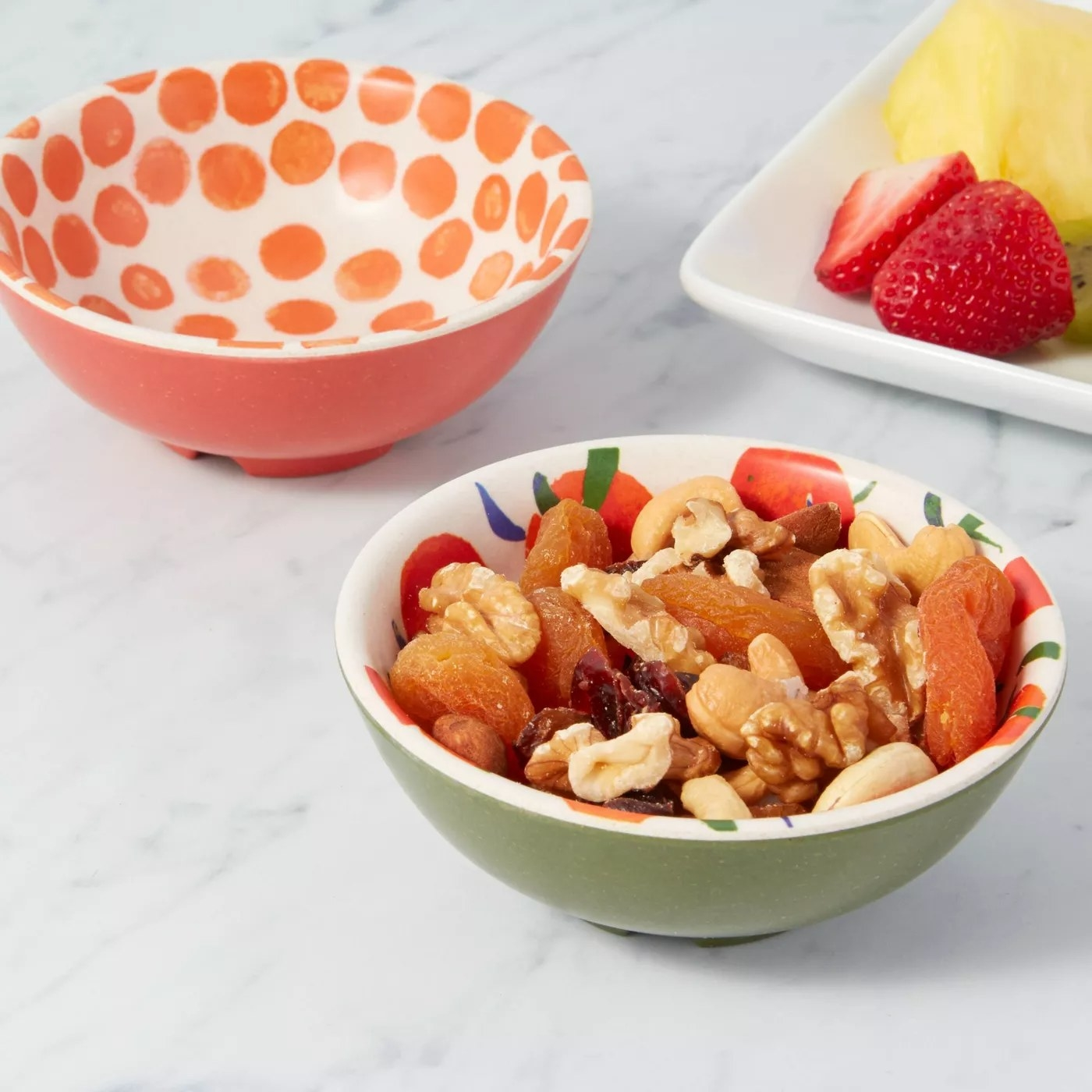 The citrus bowl is holding mixed fruits and nuts and the polka dot bowl is near a plate of fresh fruit