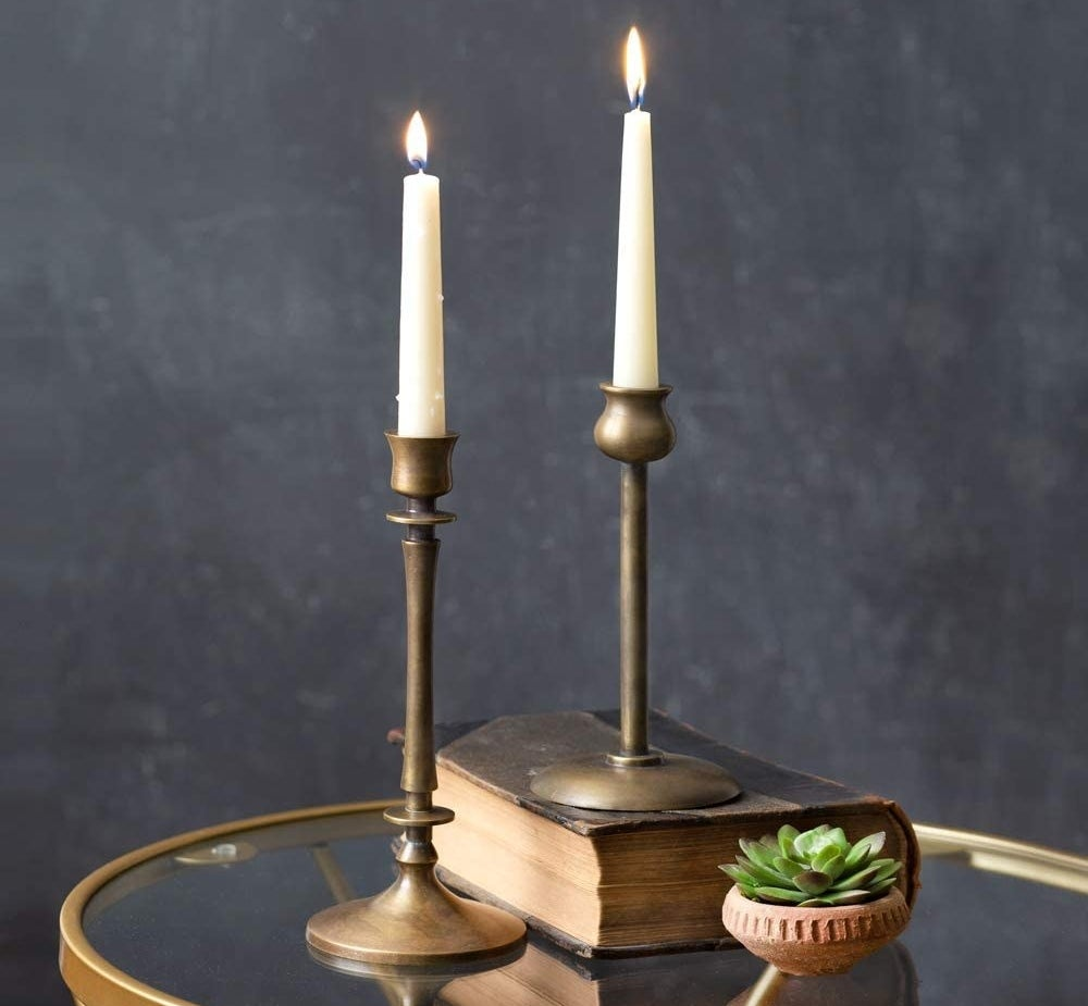 a pair of brass taper candle holders sitting on a table