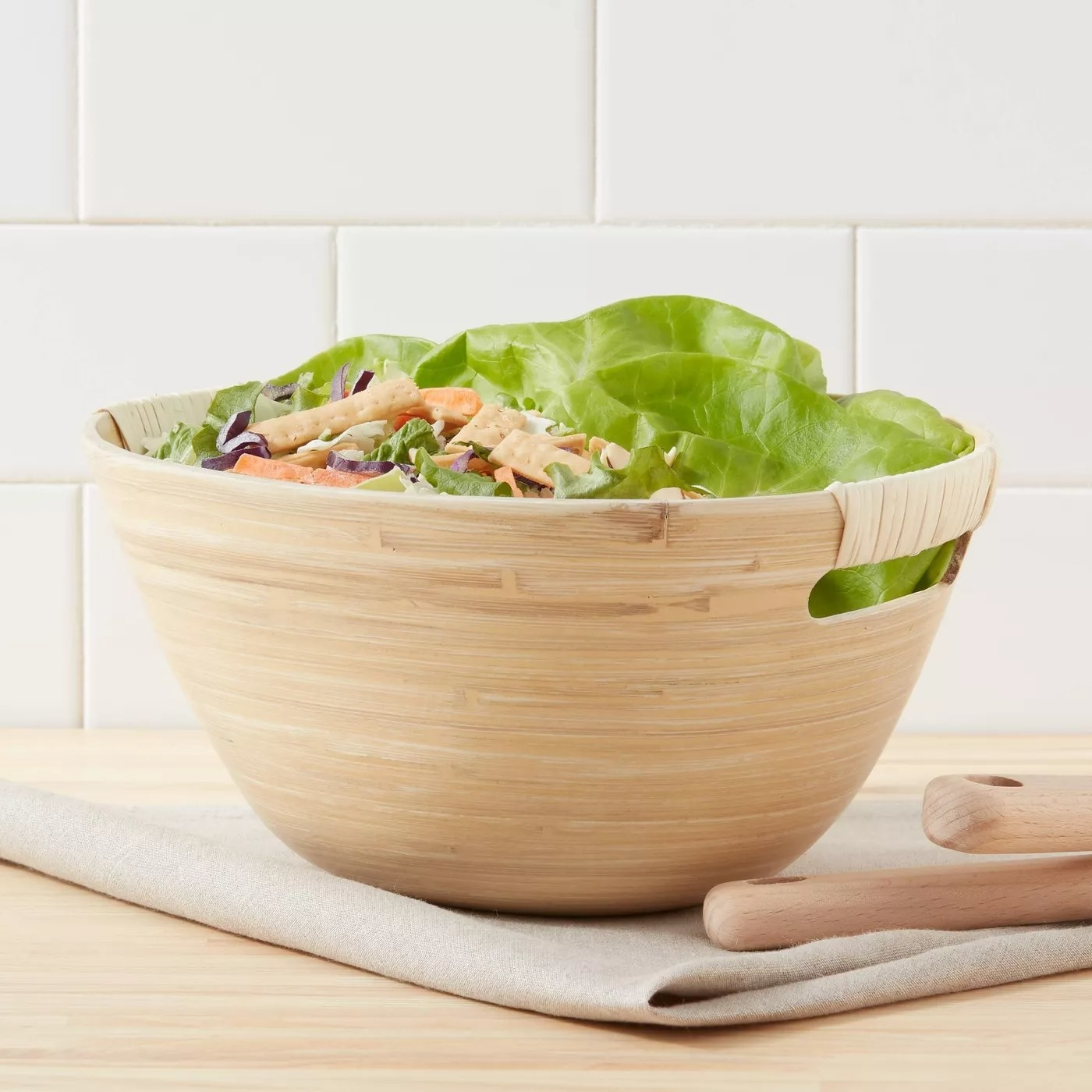 The bamboo spun serving bowl is full of salad and has utensils nearby