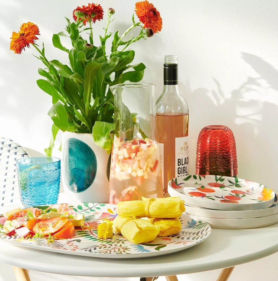 The floral serving plates are holding carious types of food and are surrounded by beverages and other decor like flowers